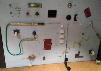 Pared sensorial en el Markthalle 8 de Bremen con elementos cotidianos como cerraduras, puertas, teléfono, tuberías, interruptores...