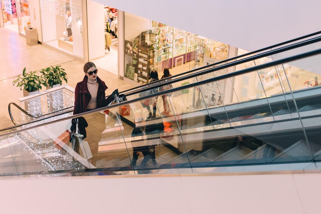 Centros comerciales en Bremen - Imagen ilustrativa mujer de compras subiendo en una escalera mecánica en un centro comercial